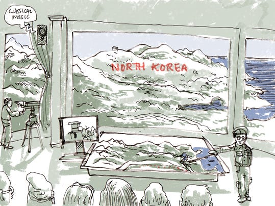 A South Korean soldier, at right, describes the view to guests at Observation Post 717 along the Demilitarized Zone (DMZ) in South Korea. (Dan Archer/Archcomix via AP)