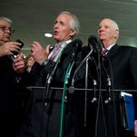 In front of a demonstrator, Senate Foreign Relations Committee Chairman Bob Corker, R-Tenn., left, and Sen. Ben Cardin, D-Md.,  discuss the Iran legislation Tuesday.
