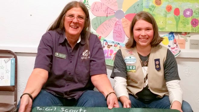 Girl Scout membership manager Annette Toney, left, sits with Aldo Leopold student Amelia Ellis with a bench that she donated.