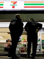 Agentes del Servicio de Inmigración y Control de Aduanas de EE. UU. presentan una notificación de auditoría laboral en una tienda de conveniencia 7-Eleven el 10 de enero de 2018 en Los Ángeles.