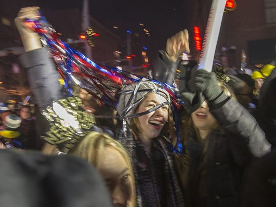 Party-goers are covered in streamers shortly after midnight during New Year's Eve on Georgia Street, downtown Indianapolis, Sunday, Jan. 1, 2017.