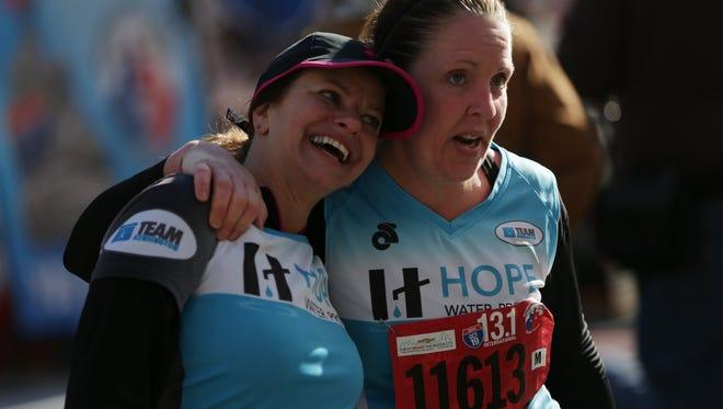 Susan Adams of Troy, left, and Deanna Nowakowski Troy react after finishing the half marathon during the 37th annual Detroit Free Press/Talmer Bank Marathon on Oct. 19, 2014.