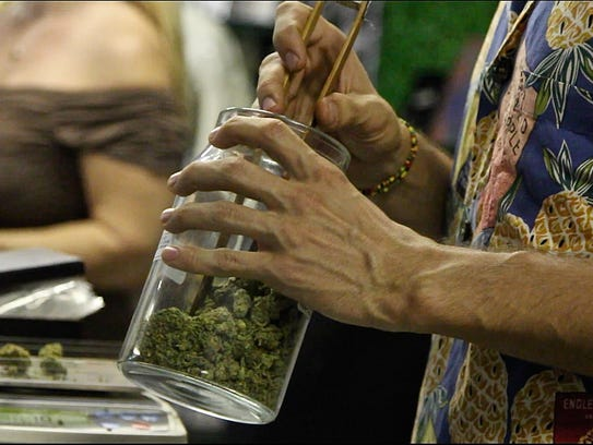 A budtender weighs cannabis for a patient at P.S.A.