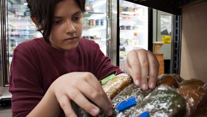 Owner of Homeschool Bakery Kyan Glover, 12, adjusts his vegan bread products on Tuesday at the Mountain View Market Co-Op.