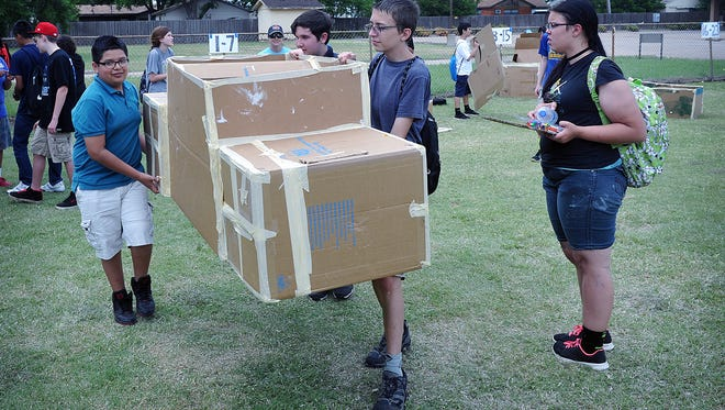 Erik Orozco, left, Christopher Brinlee, Michael Morrell and Amber McFeley prepare to store their cardboard boat after working on it Monday afternoon. The Barwise eighth graders are part of about 300 students building 70 boats using only cardboard, masking tape, caulk and paint.