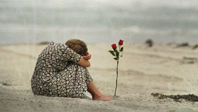 A woman sits near a rose she placed in the sand at Smith Point Park Beach in Shirley, N.Y. , on July 26, 1996 as she mourns the loss of some of her friends who were on the flight crew for TWA Flight 800.