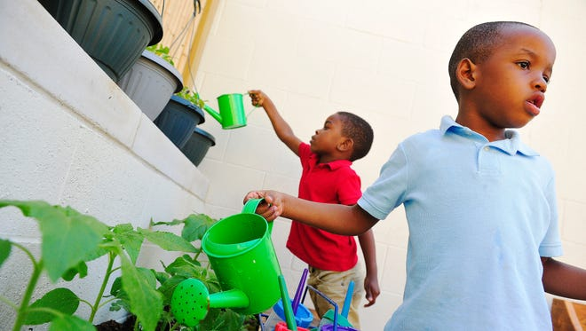 Michael Holt, left, and Ricky Robinson water the garden as part of the pre-K program at Casa Azafran on May 7, 2015.