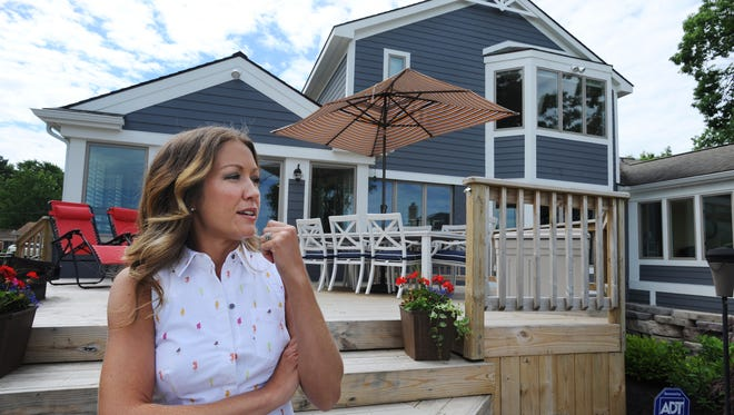 "From her deck, Dana Bennett gazes out on Sylvan Lake and the backyard of her 1953 home as she talks about its transformation from a red-brick ranch into a laid-back Michigan lake home. ""We wanted charm, not grandeur,"" says Bennett."