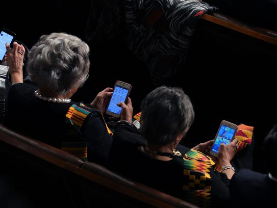 Rep. Brenda Lawrence, right, plays Candy Crush during