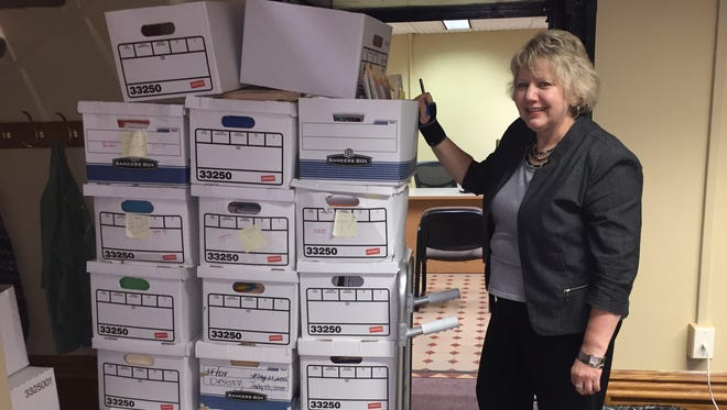 Tippecanoe County Clerk Christa Coffey stands in front of 17 boxes of papers that will soon be shredded. This is the paperwork from just one week of paper filings, which slowing are becoming obsolete with the electronic filing system. The new system frees up space and improves access to public records.