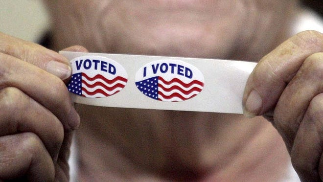 """A voter shows """"I voted"""" stickers."""