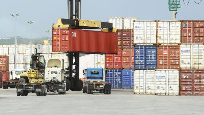 In this Aug. 3, 2015, file photo, a top-lifter container handler transports a shipping container in the storage yard of the Port Authority of Guam.