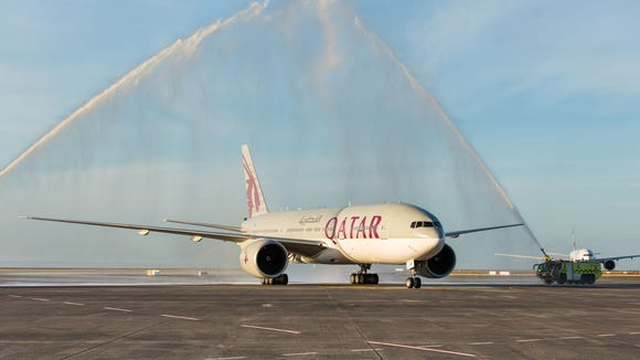 A Qatar Airways Boeing 777 receives a water-cannon