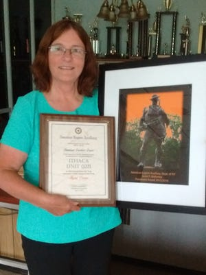 Auxiliary president Donna Mosher, from American Legion Post #221, shows off the fundraising award recently given to her group.