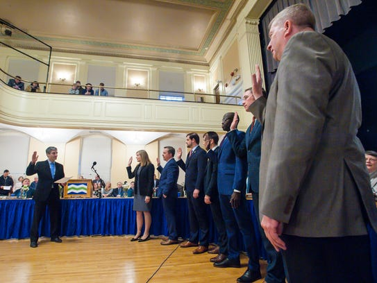 Burlington Councilor Kurt Wright, who represents the New North End, stands at right on Monday night as Miro Weinberger is sworn in for a third term as mayor, Soon after, Wright was elected Council president.