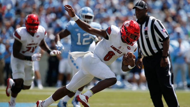 Louisville's Lamar Jackson strikes another Heisman like pose as he struggles to remain on his feet during a 43 yard touchdown run against North Carolina. Sept. 9, 2017