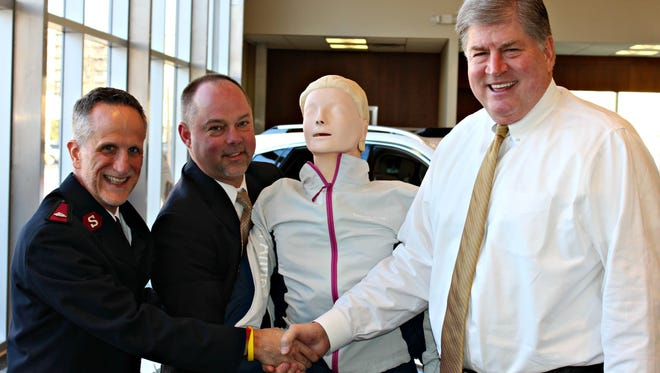 Salvation Army Major Larry Ashcraft, left, accepts the CPR mannequin from Charlie Howard, second from left, executive vice president of the Greater Cincinnati Automobile Dealers Association, and Chris MacConnell, right, president of Thomson-MacConnell Cadillac.