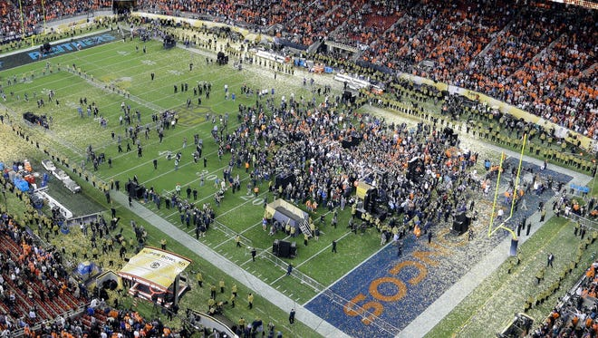 Players and people gather on the field after the NFL Super Bowl 50 football game between the Denver Broncos and the Carolina Panthers Sunday, Feb. 7, 2016, in Santa Clara, Calif. The Broncos won 24-10.