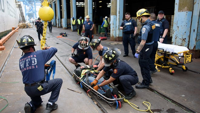 An injured worker on a vessel at the Port of Wilmington was packaged and lifted out of the boat by a crane Saturday.