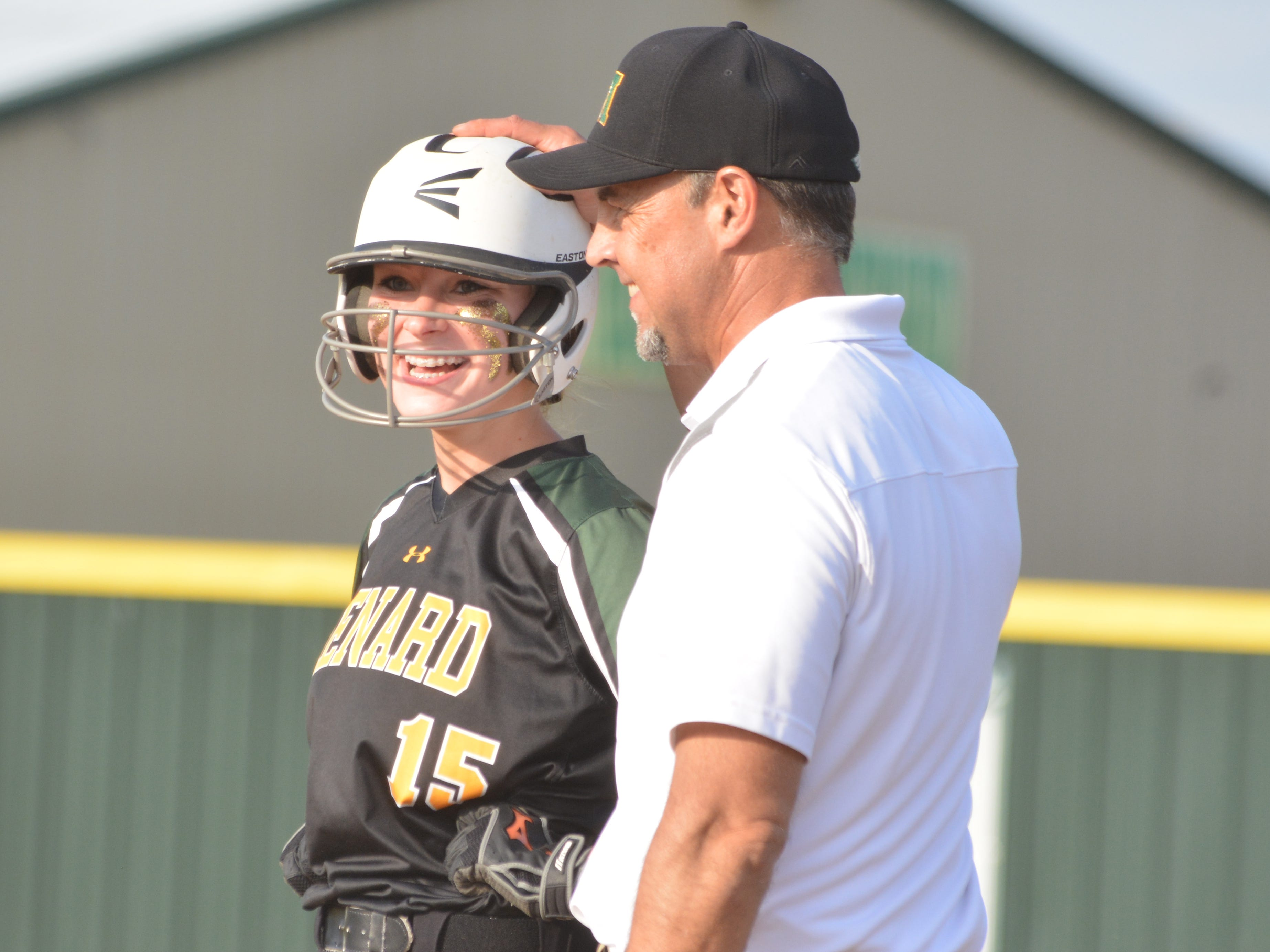 Madalyn Mahfouz (15, left) smiles as assistant coach Mark Vilar pats her head after Mahfouz's first base hit brought in a run Thursday.