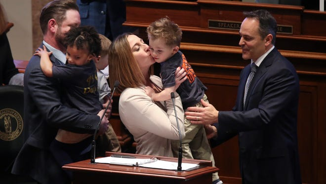Ashley Dearinger, center, kissed Grant, 3, as Gov. Matt Bevin, right, looked on during his State of the Commonwealth address.  Bevin invited the Dearingers, including her husband Heb Dearinger, left, along with Paige, 3, and Grayson, 2, (partially obscured) to speak during his address about the benefits of adoption.  The Dearingers adopted all three children.  They are from Louisville.