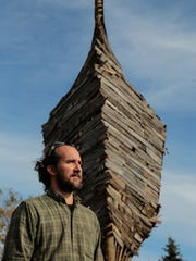 Detroit artist Scott Hocking stands near the front of his latest art piece turning a dilapidated barn into an upside down Ark at a farm in Port Austin on Friday October 23, 2015.