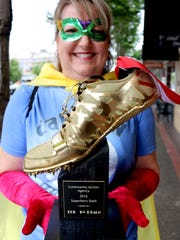Cindy Leinassar (Captain Awesome) displays a trophy to be awarded to top finishers in all divisions of the Superhero Dash.