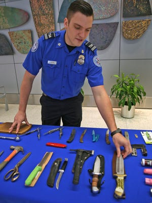 Supervisor Security Transportation Officer Jay Thompson shows some of the recent items, Thursday, Dec. 14, 2017, confiscated from travelers going through security at the Indianapolis International Airport.