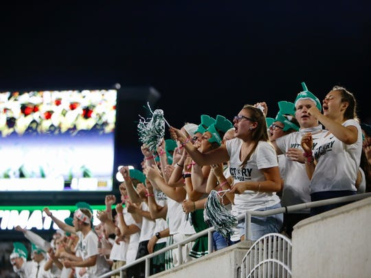 Michigan State football fans cheer as the Michigan State marching band takes the field.