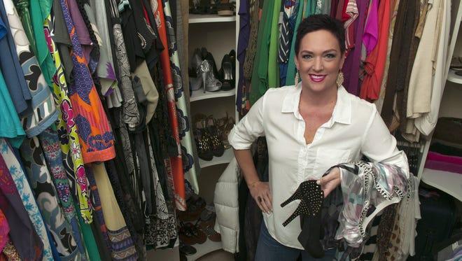 Angela Wilson stands with an assortment of clothing and accessories found in her Naples home closet.