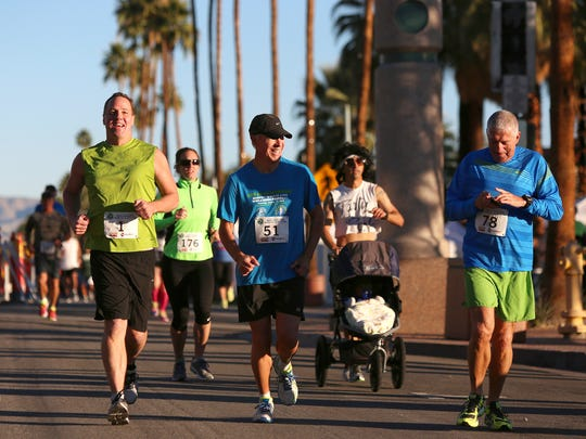 Palm Springs mayor Steve Pougnet, left, and Robert Bryant smile as they run down Palm Canyon Drive in Palm Springs during the Mayor's Healthy Planet Healthy You 10 Mile Race on Saturday.
