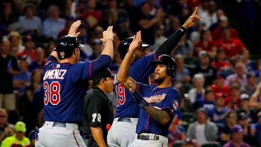 Minnesota Twins' Chris Gimenez (38), Byron Buxton (25) and Kennys Vargas, rear, celebrate scoring on a bases clearing double by Brian Dozier in the fifth inning of a baseball game against the Texas Rangers in Arlington, Texas, Monday April 24.