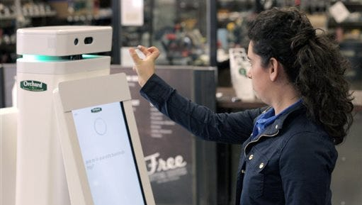 In this undated image provided by Lowe's, a woman holds a nail up to be scanned by an OSHbot robot. The robots are equipped with 3D cameras so they can scan and identify items. And customers can research items they want to buy on their screen. Then the robot can lead them to the aisle where an item is located.
