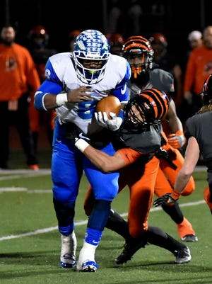Winton Woods' Kenny Mayberry (8) works to break out of a Massillon-Washington tackle, Nov. 24, 2017.
