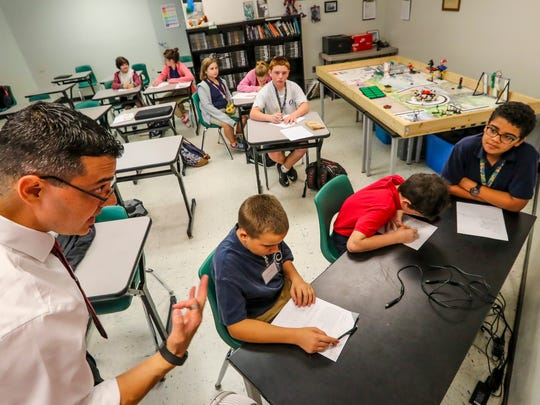 Golden Apple winner Richard Romano is a teacher at North Fort Myers Academy for the Arts. Tuesday morning he was having the students dissect a poem.  He works with three of the newer students in class that have never done this before.