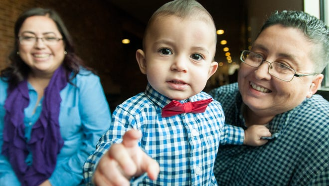Zoilo Chacon-Maldonado, 17 months, hangs out with his newly adoptive parents Jessica Chacon, left, and Liza Maldonado on Monday during an adoption event in recognition of National Adoption Month. The event is organized by the CYFD Foster Care/Adoptions Licensing Unit and 3rd Judicial District Court Chief Judge Fernando Macias.