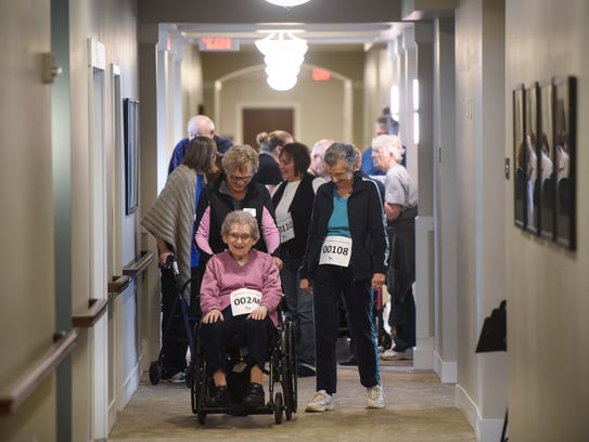 Residents and volunteers make their way down a hallway