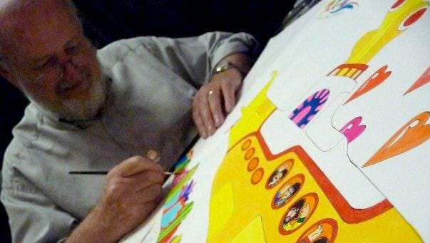 "Classic cartoonist Ron Campbell is shown drawing on a piece depicting a scene from The Beatles animated movie ""Yellow Submarine."""
