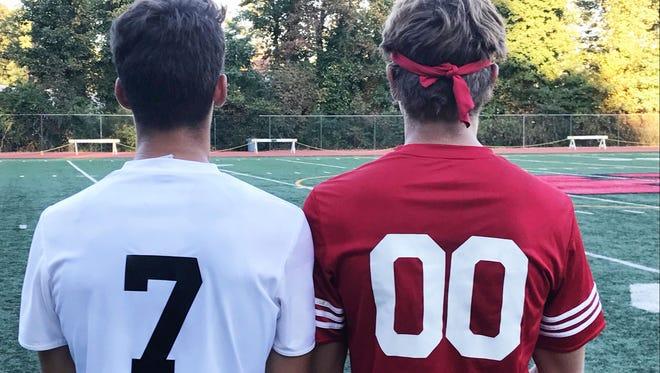 Haddonfield junior midfielder Luke Baxter, left, and senior keeper Finn Miller, right, pose in their jerseys to commemorate the Haddons' 700th win in program history.