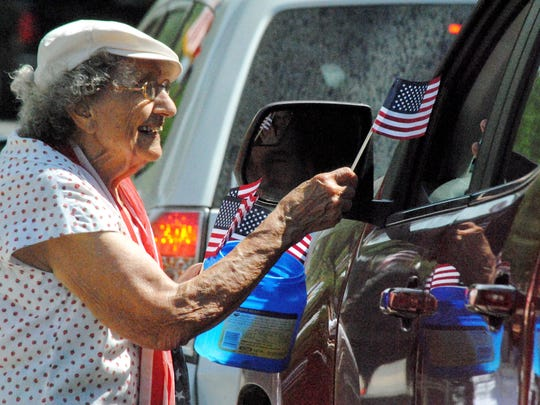 Anna Marie Quinlan, 92, gets a donation for a flag during Saturday's fundraiser.