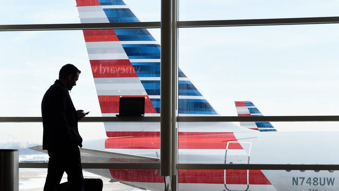 A passenger talks on the phone as American Airlines jets sit parked at their gates at Washington's Ronald Reagan National Airport on Jan. 25, 2016.