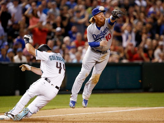Los Angeles Dodgers' Justin Turner (10) jumps for a wide throw as Arizona Diamondbacks' Paul Goldschmidt (44) slides into third base during the seventh inning of a baseball game Friday, April 21, 2017, in Phoenix. Goldschmidt was forced to go back to second base on a ground-rule-double call. The Diamondbacks defeated the Dodgers 13-5. (AP Photo/Ross D. Franklin)