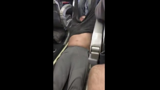 This April 9, 2017, image made from a video provided by Audra D. Bridges shows a passenger being removed from a United Airlines flight in Chicago.