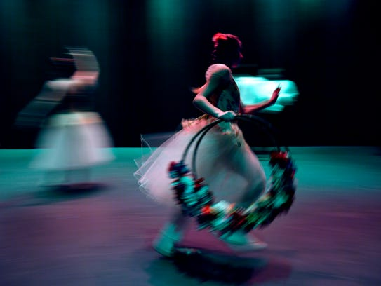 """Hannah Flatt runs across the stage at HSU's Behrens Auditorium carrying a pair of flower hoops between acts Friday. Dance, Ltd.-School of Dance held its spring show over the weekend, """"Gala Performance & Hansel and Gretel,"""" which featured nearly 60 students of varying ages."""