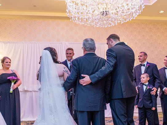 Robert Fisher walks his daughter Nichole down the aisle at her wedding in November, just three months after he underwent heart and kidney transplants.