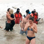"Actor Taylor Kinney, center left, holds his fiancée, pop star Lady Gaga, as they and members of the ""Chicago Fire"" cast take part in the Chicago Polar Plunge at North Avenue Beach on Sunday in Chicago."