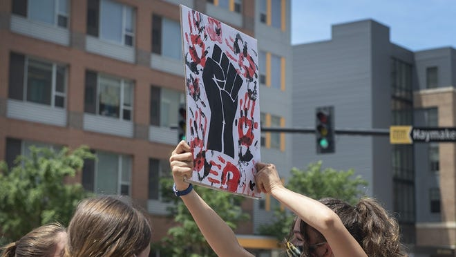 Clara MacPherson, 15, turns a sign while protesting outside of the Kent Police Department on Wednesday. Kent Roosevelt students Maddie Walker and Ava Hoover organized the protest in support of the Black Lives Matter movement.