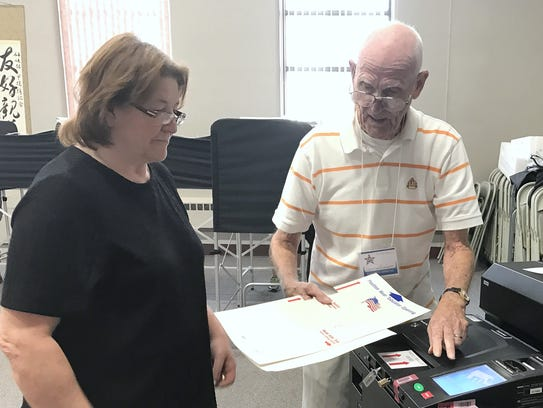 Poll worker George Everett helps resident Sue McCarty