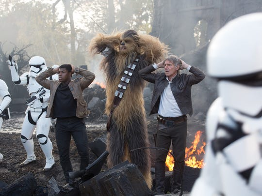 Finn (John Boyega, left), Chewbacca (Peter Mayhew) and Han Solo (Harrison Ford) are surrounded by First Order Stormtroopers in 'Star Wars: The Force Awakens.'
