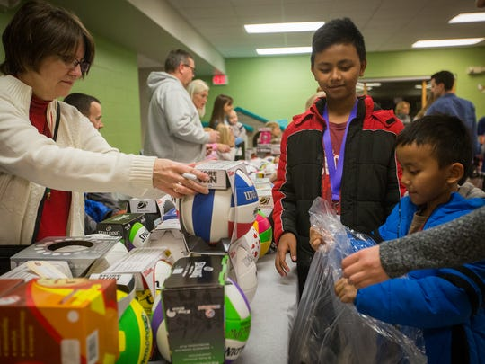 Kay Riggins of Ankeny, left, hands a volleyball to Van Lal, 7, and his cousin Lal Muan, 13, as they shopped for toys at Zion Lutheran Church in Des Moines, Wednesday, Dec. 16, 2015. The church gave away presents to 600 children.
